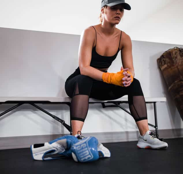 Woman sitting on bench, with boxing gloves on the floor, waiting for her self defense class