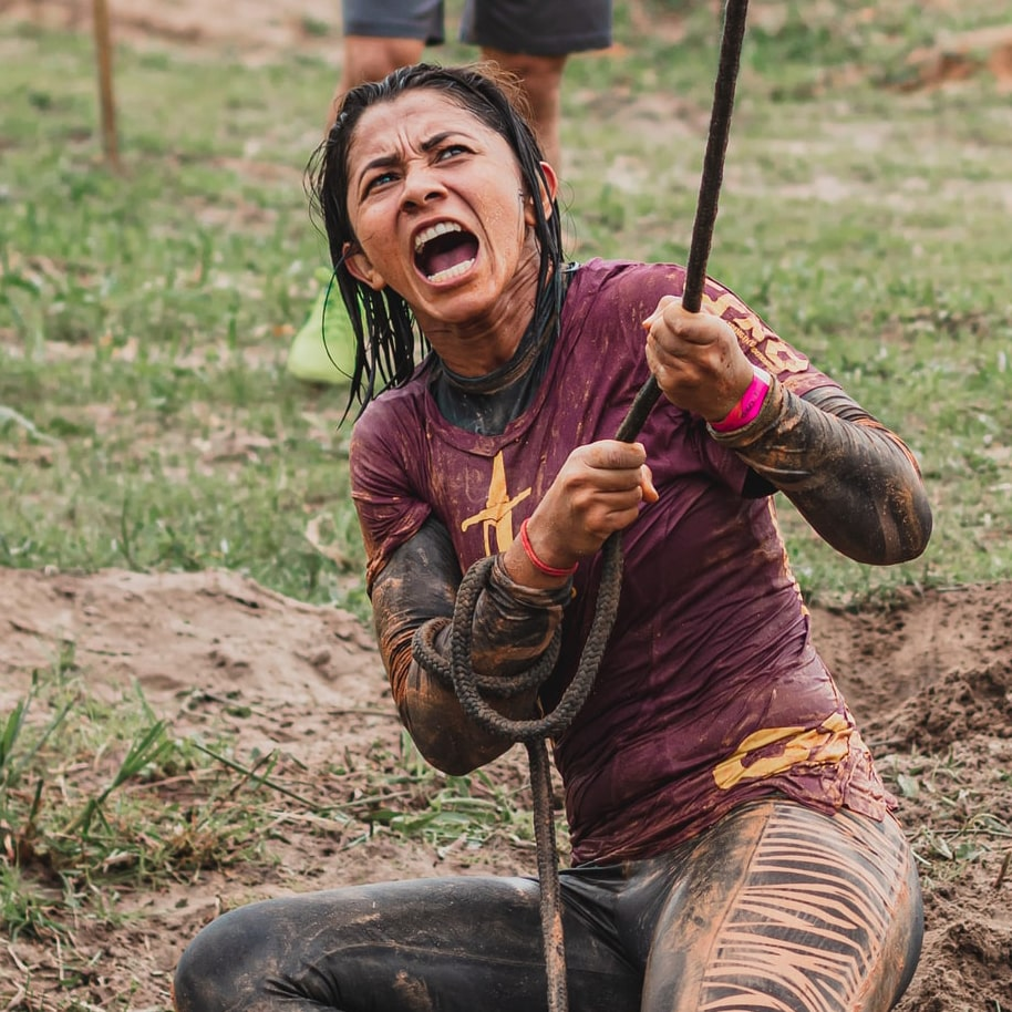 A woman showing her strength as she fights with a rope.